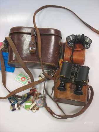 A collection of vintage leather cased binoculars, a Leica camera and other assorted leather cases