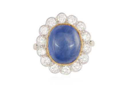 A SAPPHIRE AND DIAMOND CLUSTER RING, The oval-shaped cabochon sapphire weighing approximately 8.