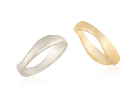 TWO GOLD RINGS, of wavy design, one mounted in 18K white gold, and the other mounted in 18K yellow