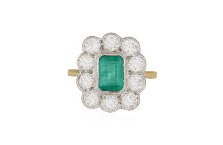 AN EMERALD AND DIAMOND CLUSTER RING, the cut-cornered rectangular-cut emerald within collet-setting,