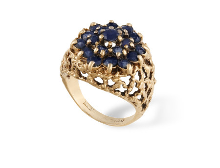 A SAPPHIRE COCKTAIL RING, CIRCA 1960, of openwork bombé textured gold design, centrally-set with