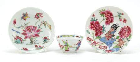 Chinese porcelain teaware comprising a tea bowl and two saucers, each hand painted in the famille