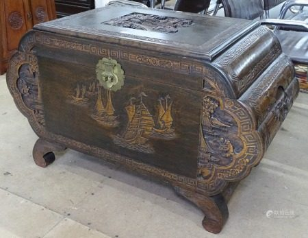A Chinese camphorwood blanket chest, of shaped form, with relief carved decoration, on scrolled