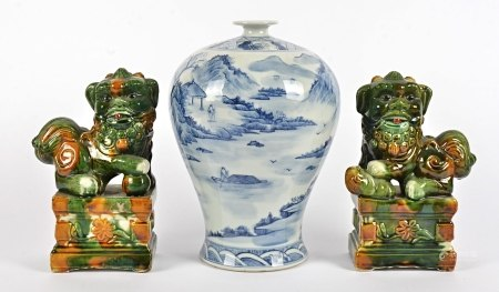 A pair of Chinese sancai glazed Dogs of Fo raised on plinths, each holding an object underfoot,