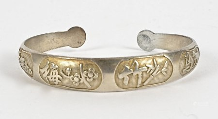 A Chinese silver bangle, decorated with flowers, bamboo, a horse, and calligraphic symbols, widest