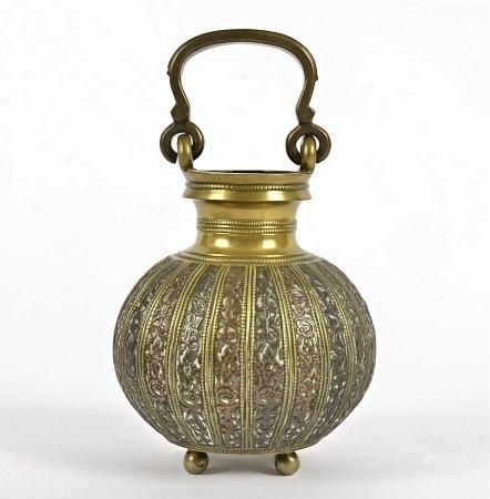 A Middle Eastern brass vessel, on tripod feet, height 19cm