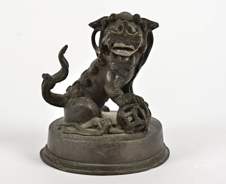 A 19th Century Chinese bronze figurine, modelled as a male dog of Fo, on a circular base with
