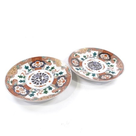 A pair of Chinese porcelain plates, with hand painted and gilded bird decorated panels, diameter