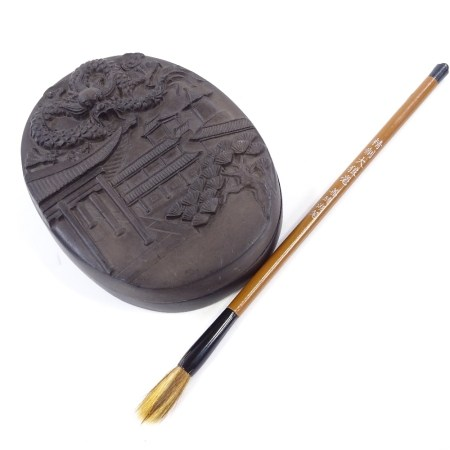 A Chinese ink stone and cover, with relief moulded lid, length 14cm, and brush