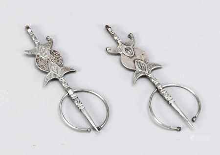 Pair of large fevers, Morocco, 1st third of the 20th century, silver. Bordered by 2 flower