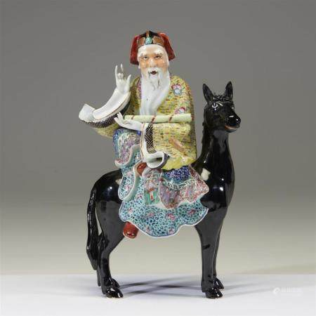 A Chinese enameled porcelain figure of Zhang Guolao on a bla
