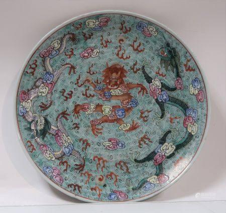Assiette en porcelaine à décor de dragons à la poursuite de la perle sacrée sur fond vert. Chin
