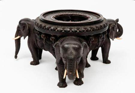 An Anglo-Indian carved animal wine coaster in the form of el