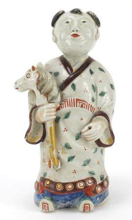Chinese porcelain figure of a boy holding a toy horse hand painted with leaves, 20.5cm high :For