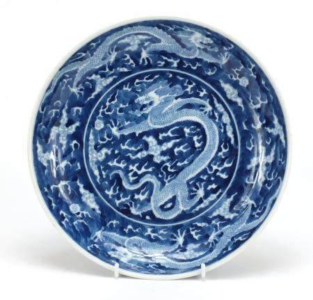 Chinese blue and white porcelain shallow dish hand painted with dragons amongst clouds chasing a