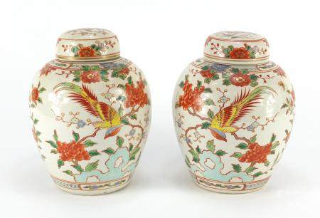 Pair of Chinese porcelain jars with covers, each hand painted with birds of paradise amongst