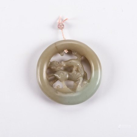 A CHINESE CELADON JADE 'QILIN' PENDANT Circular, carved to the centre with a horned qilin trotting
