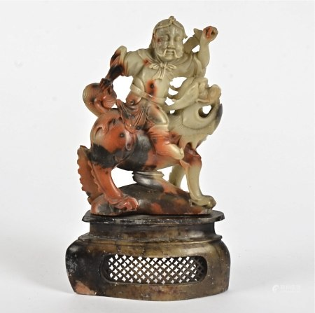 A 19th Century Chinese soapstone carved figure, modelled as a seated warrior upon a mythical