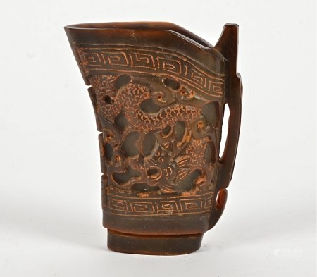 A Chinese horn libation cup with dragon to each side and key fret border, probably mid 20th