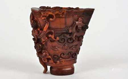 An early 20th Century Chinese carved horn libation cup, the design with multiple raised crawling