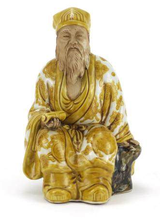 Chinese porcelain figure of seated Emperor holding a scroll, hand painted with Daoist emblems,