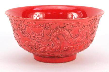 Chinese red ground porcelain bowl decorated in relief with dragons amongst clouds, six figure