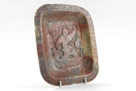 A Chinese rectangular soapstone dish, late 19th/early 20th century, carved with a figure of a