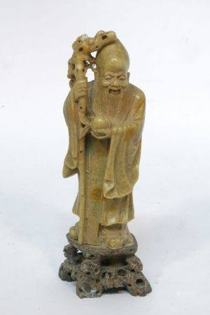 A Chinese soapstone figure of Shou Lao, early 20th century, carved holding a peach and an ancient