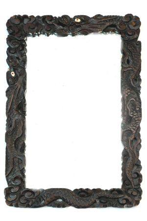 Two Chinese hardwood mirrors carved with the forms of dragon heads and scrolling decorative designs,