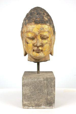 A Tang style carved and parcel gilt head of Buddha, 20th century, modelled with stylised hair and