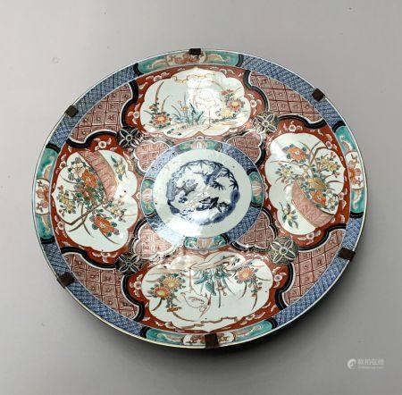 JAPON. Grand PLAT circulaire en porcelaine à décor polychrome de paniers fleuris et d'échassier