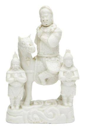 A Chinese blanc de chine figure group, Kangxi period, modelled as Guandi on horseback beside two