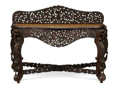 A Colonial Burmese teak side table, late 19th century, profusely carved to the back and apron with