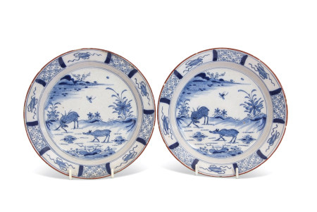 Pair of 18th century Dutch Delft plates, the centre painted in Chinese porcelain Kangxi style with