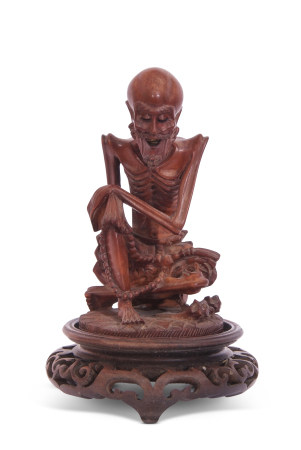 Oriental wooden carving of a sage or elderly gent seated on a wooden oval base, 13cm high