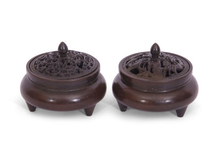 Two small Chinese bronze censers with pierced covers and six character reign mark to base, raised on