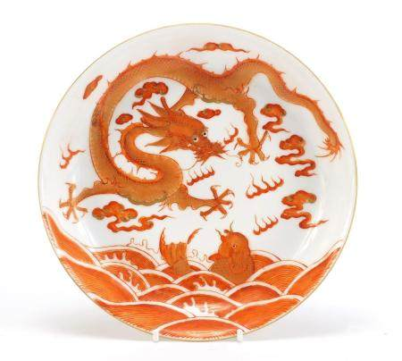 Chinese porcelain shallow dish hand painted in iron red with a dragon amongst clouds and fish in