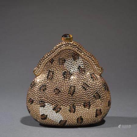LANDAUMinaudière en métal doré, entièrement pavée de petits strass façon panthère, anse chaîne
