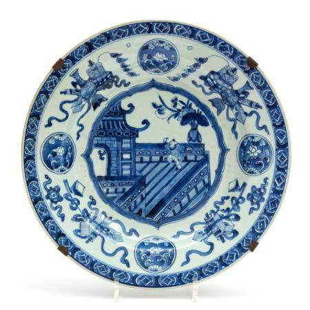 A large blue and white plate with a jumping boy