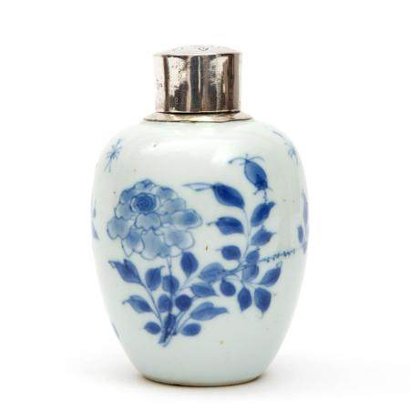 A blue and white tea canister with silver top