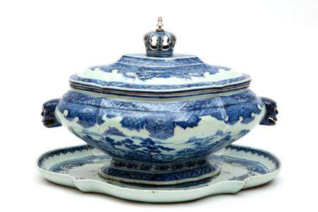 A large blue and white tureen with crown knob and under tray