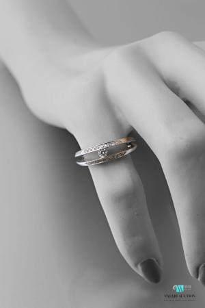Bague en or gris 750 millièmes formée de deux anneaux retenant au centre un brillant d'environ