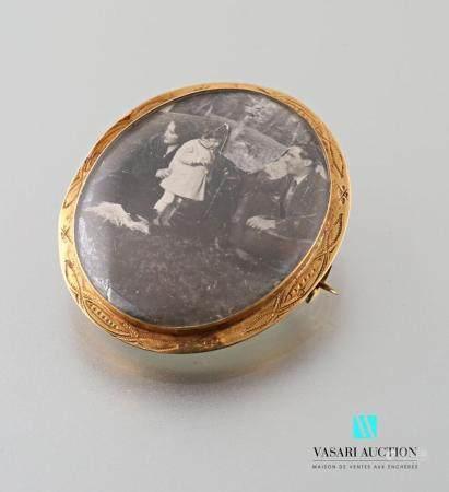 Broche ovale en or jaune 750 millièmes, le pourtour ciselé, le centre serti de verres avec un s