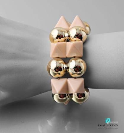 Bracelet sur cordon élastique orné de perles et motifs pyramidals en plastique.