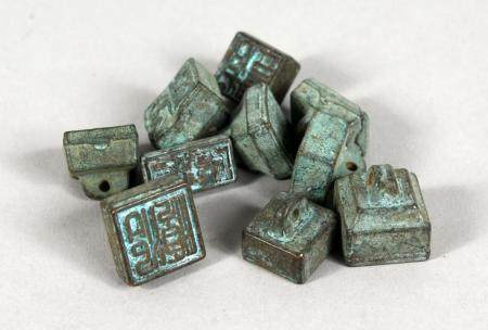 A SET OF TEN CHINESE BRONZE MINIATURE SEALS. 0.5ins wide.