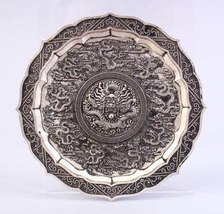 A CHINESE WHITE METAL DRAGON DISH, decorated with many drago