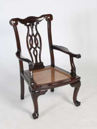 A Chinese dark wood armchair of Western style, Qing Dynasty, the scroll carved top rail enclosing an