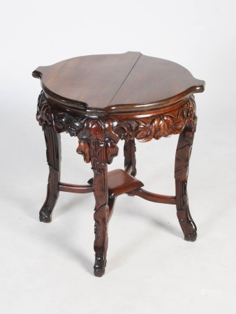 A Chinese dark wood fish bowl stand, Qing Dynasty, the shaped circular top above a foliate carved