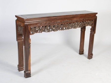 A Chinese dark wood altar table, early 20th century, the panelled rectangular top above a relief