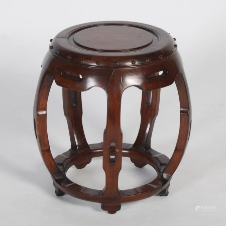 A Chinese dark wood barrel shaped stool, 20th century, the circular panelled top within a studded